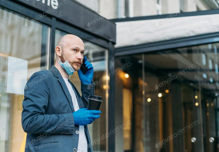 Adult bald bearded man in medical face mask and rubber gloves with paper cup of coffee