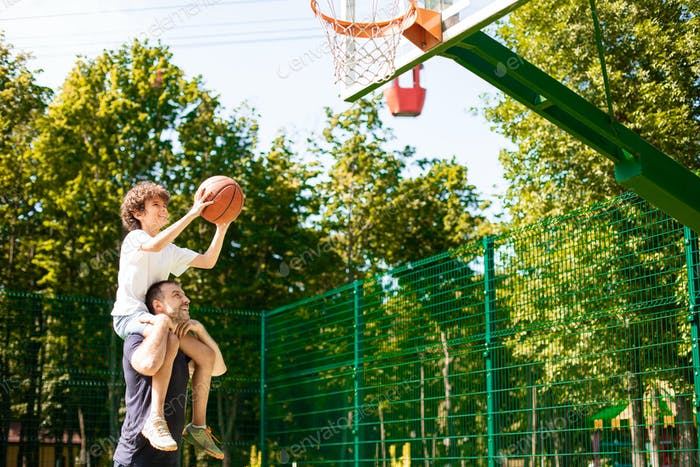 Man holding little boy on shoulders, playing basketball