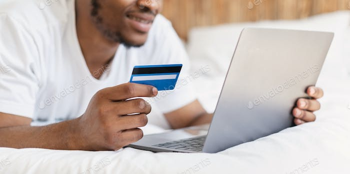 Black Man Shopping Online With Laptop And Credit Card Indoor