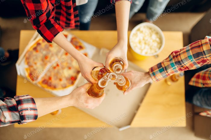 Friends clink bottles over the table with pizza