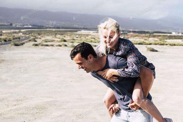 Хорошая счастливая молодая кавказская пара, играющая вместе, веселившись и смеясь