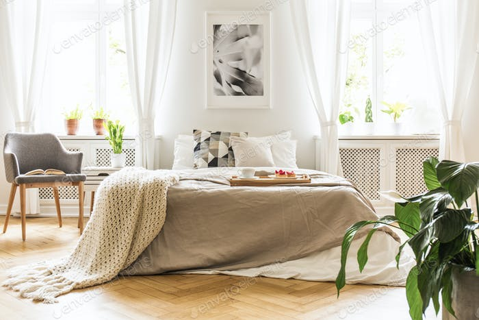 Open book on a gray, wooden armchair by a cozy bed with breakfas