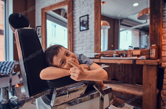 Lustiger Junge zeigt seine Finger, während er auf einen Friseur im geschäftigen Barbershop wartet.