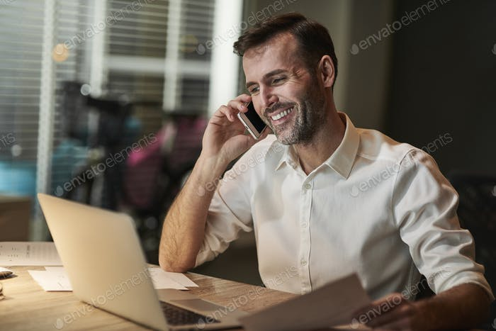 Smiling businessman talking by mobile phone
