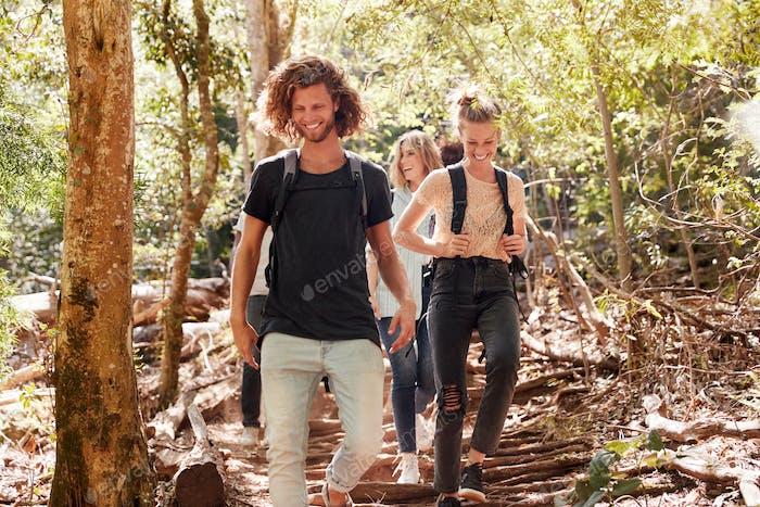 Millennial Freunde wandern gemeinsam bergab auf einem Waldweg, voller Länge