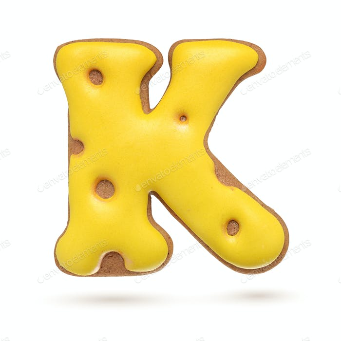 Capital letter K yellow gingerbread biscuit isolated on white.