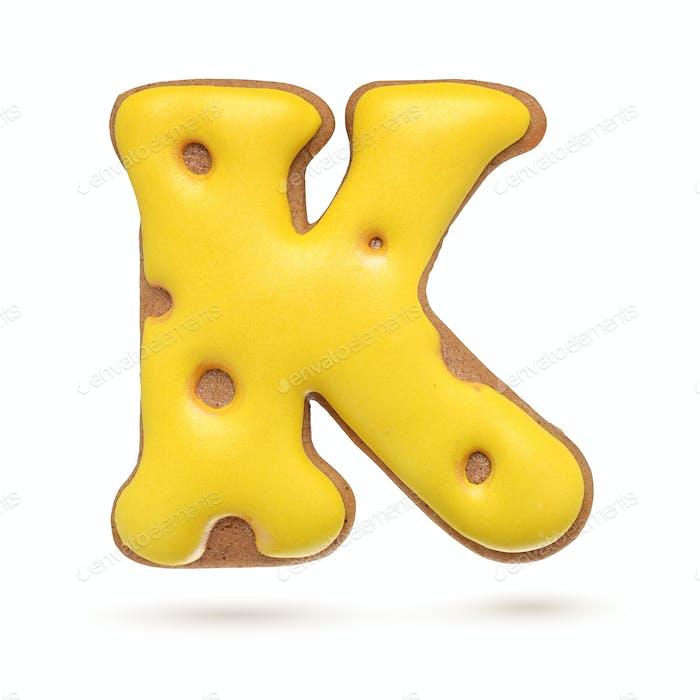 Großbuchstabe K gelber Lebkuchenkeks isoliert auf weiß.