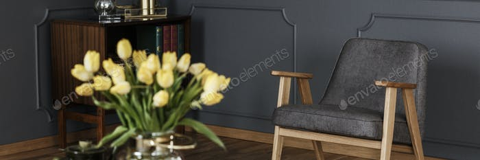 A modern gray armchair in a dark living room interior with woode