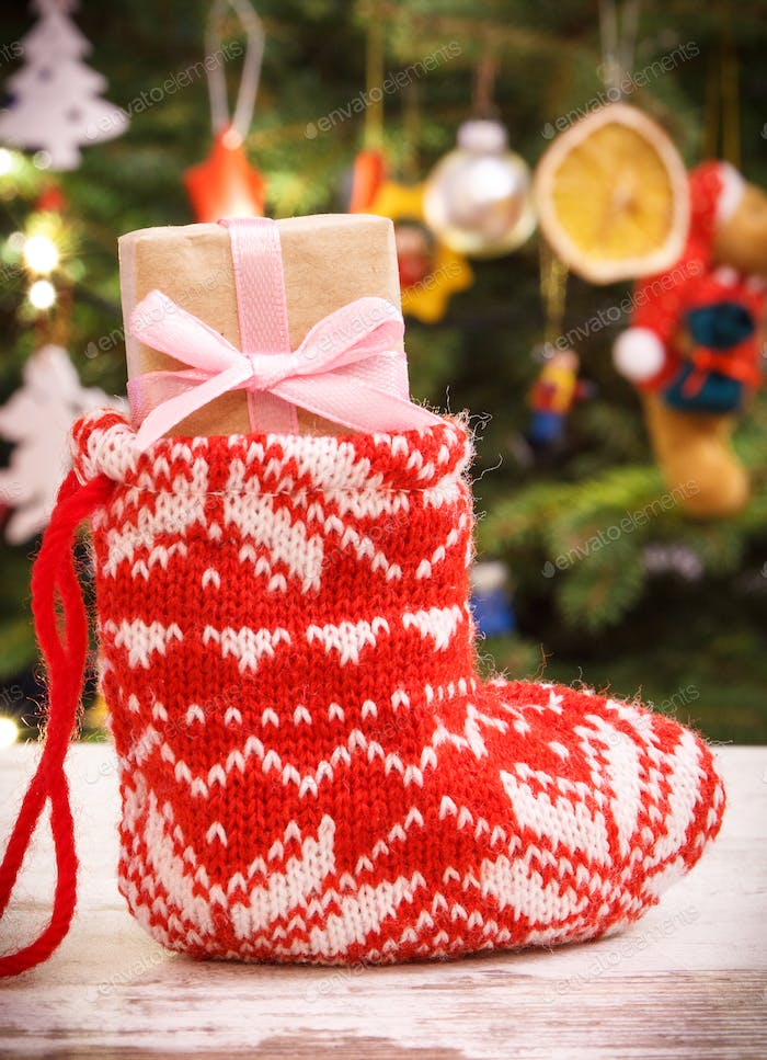 Wrapped gift with ribbon for Christmas in red sock on background of christmas tree with decoration