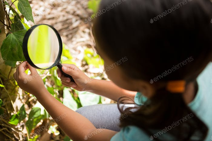 Little girl exploring nature through magnifying glass