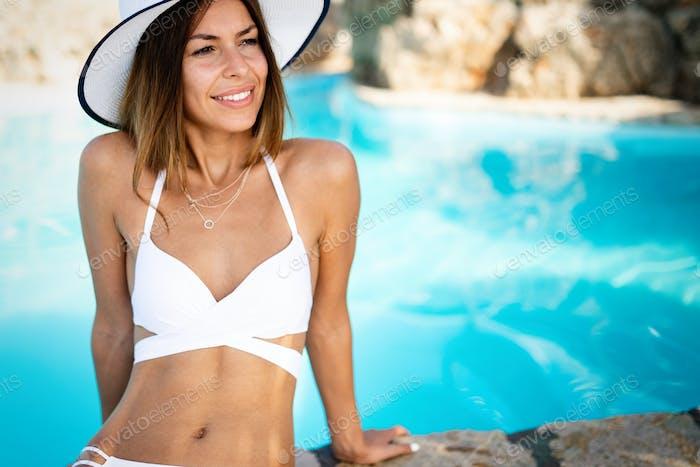 Happy fit woman in bikini and sunhat on sea beach