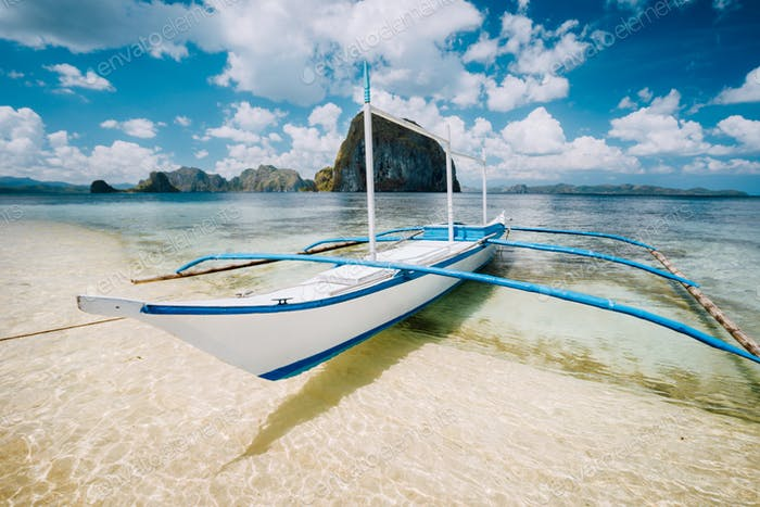 White banca boat on the sandy beach ready for island hopping trip. Amazing Pinagbuyutan island in