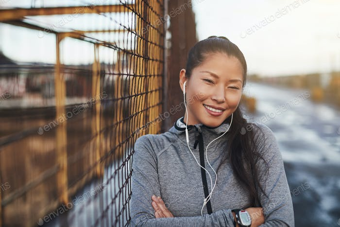 Young Asian woman in sportswear listening to music before jogging
