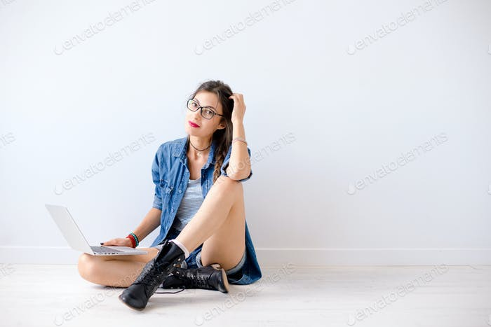 Smiling young woman holding a laptop on her crossed legs
