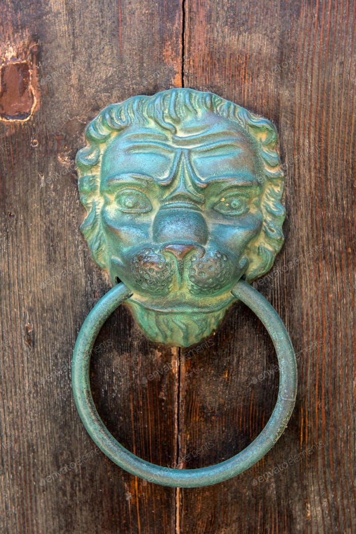 Old brazen lion head door knocker on a wooden door. Mdina, Malta