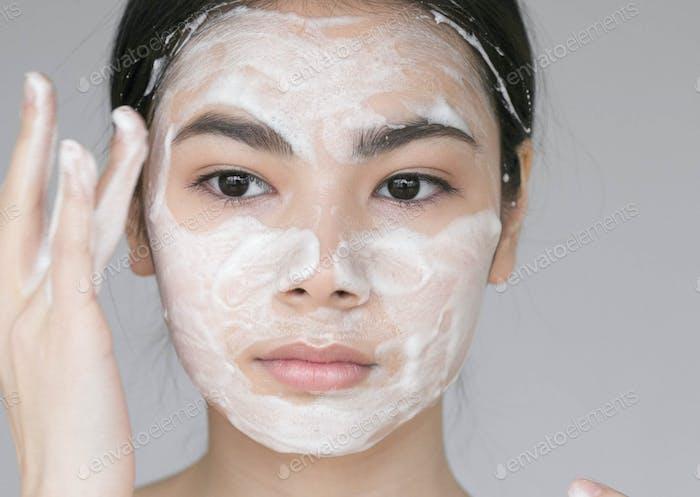 Мыло лицо Молодая красивая женщина моет лицо