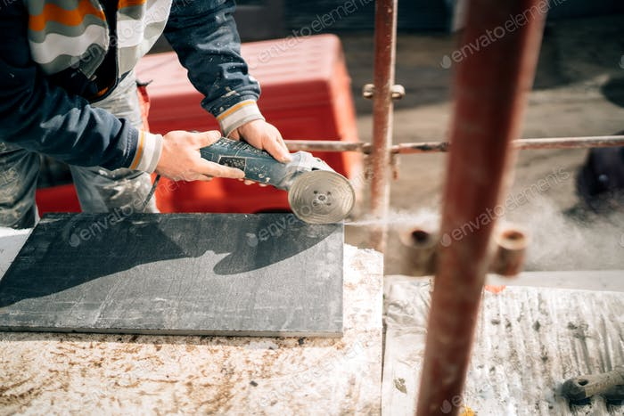 Construction site details - industrial tool, hand grinder of worker cutting marble