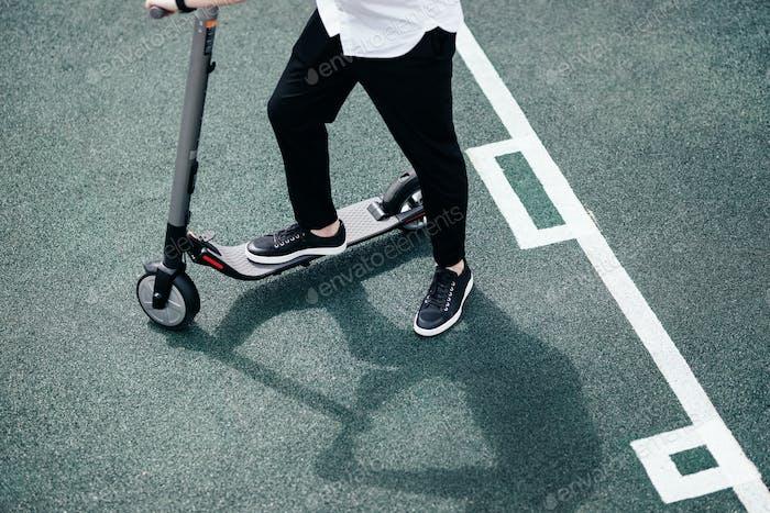 Beine eines Mannes im stilvollen Outfit stehen auf Elektroroller auf der Straße