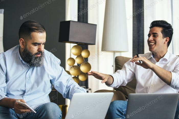 Young man laughing near bearded colleague