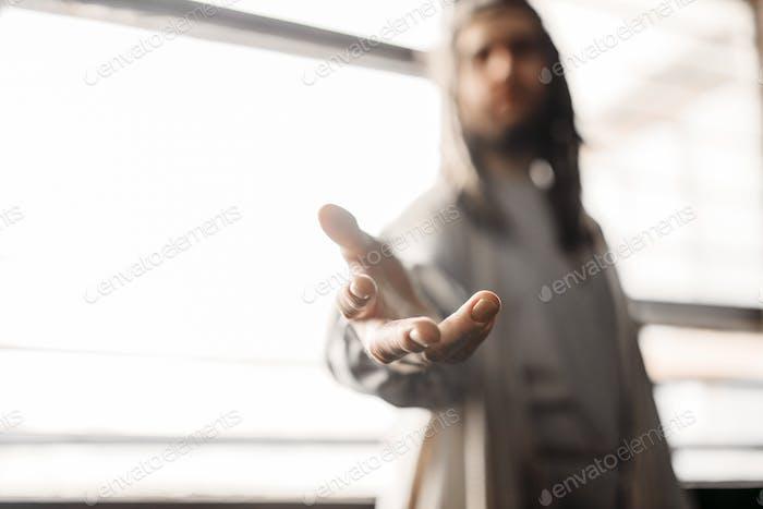 Jesus Christus in weißem Gewand streckt seine Hand heraus
