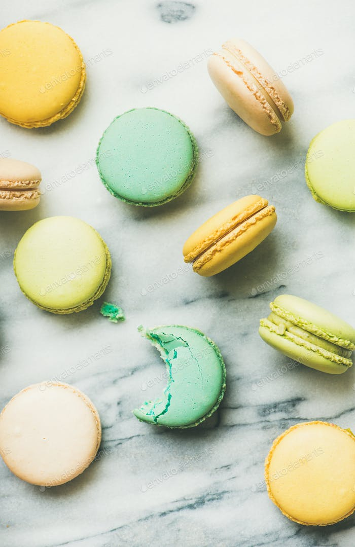 Colorful French macaroons over grey marble background, vertical composition