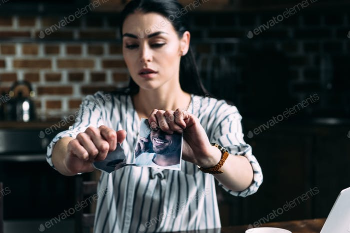 depressed young woman tearing photo of ex-boyfriend