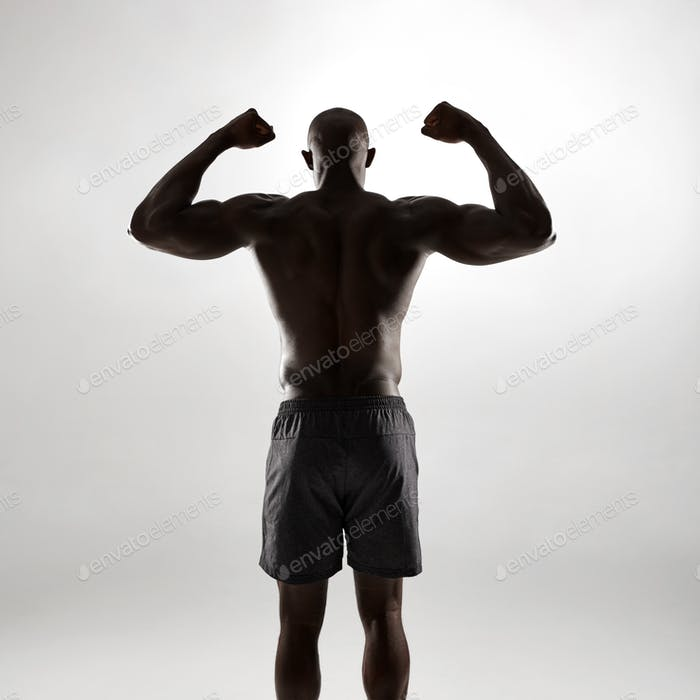 Shirtless fitness model flexing arms in silhouette