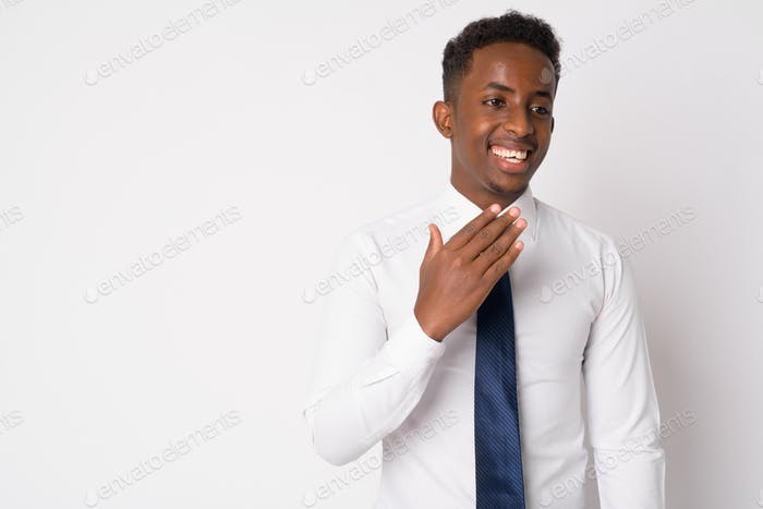 Portrait of happy young African businessman thinking and laughing
