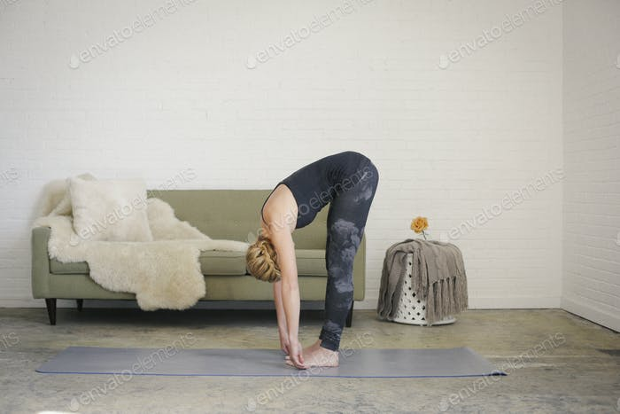 A woman bending down in a yoga pose, touching her toes.
