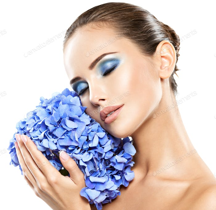 Closeup face of young beautiful woman with a blue makeup of eyes