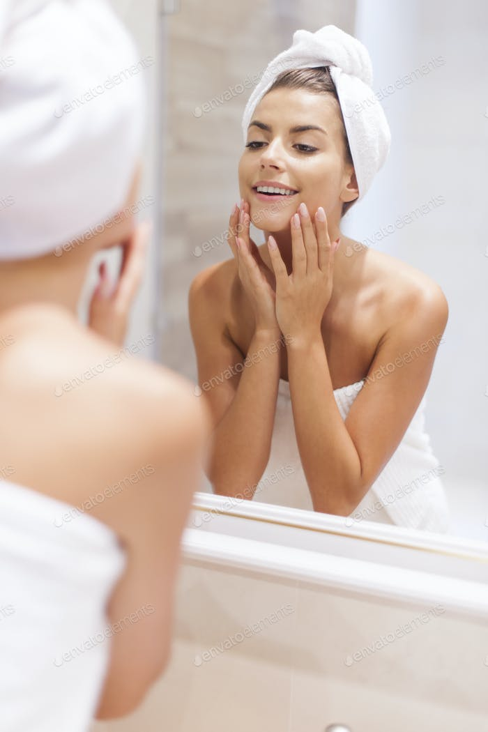 Woman looking on reflection in the mirror after shower