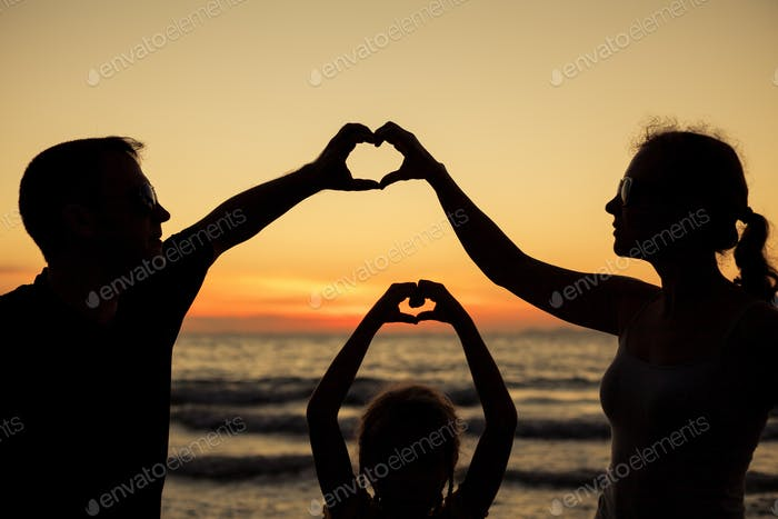 Silhouette der glücklichen Familie, die am Strand in der Sonne spielen