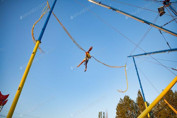 Kleines Mädchen fliegt auf Gummibändern und springt auf einem Trampolin