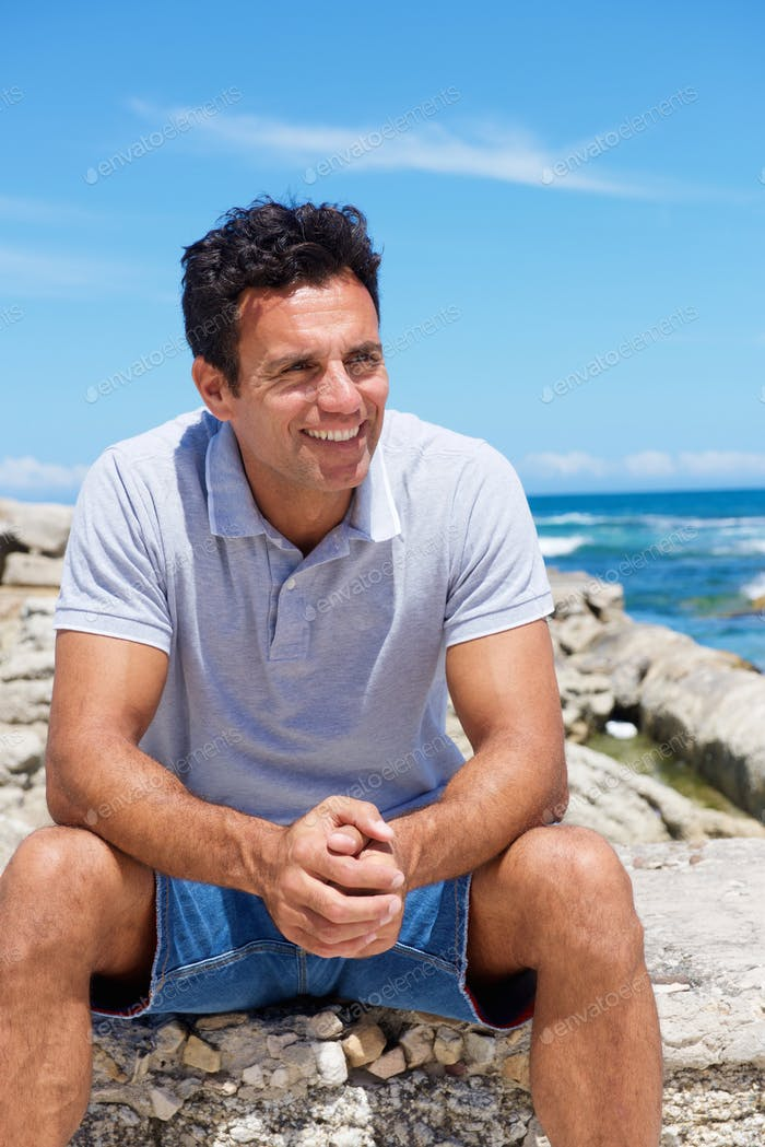 Smiling middle aged man sitting by the beach