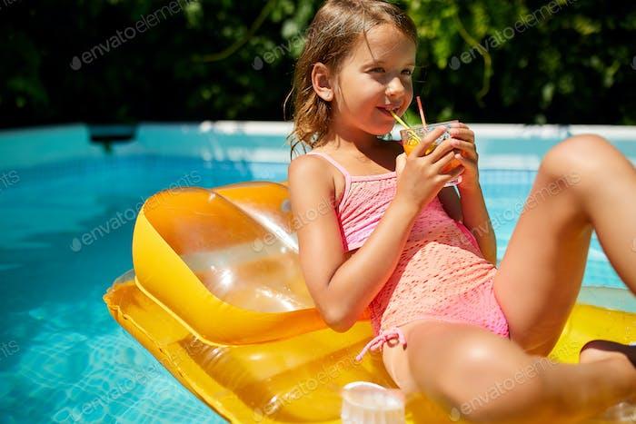 Little girl relaxing in swimming pool