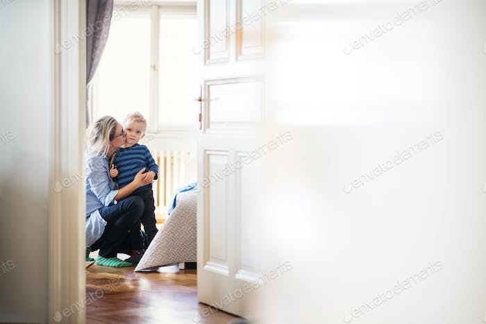 Young mother kissing her toddler son inside in a bedroom. Copy space.