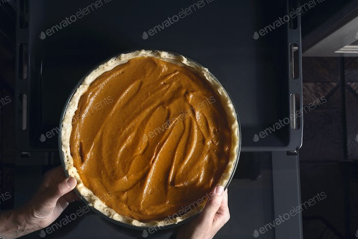 Putting pumpkin pie in the  oven top view