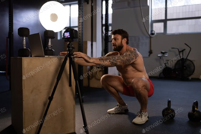 Fitness instructor squatting near camera and laptop