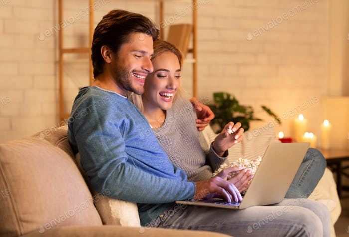 Spouses Using Laptop Watching Film Eating Popcorn Relaxing At Home