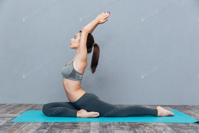 Healthy pretty brunette is exercising yoga on grey background