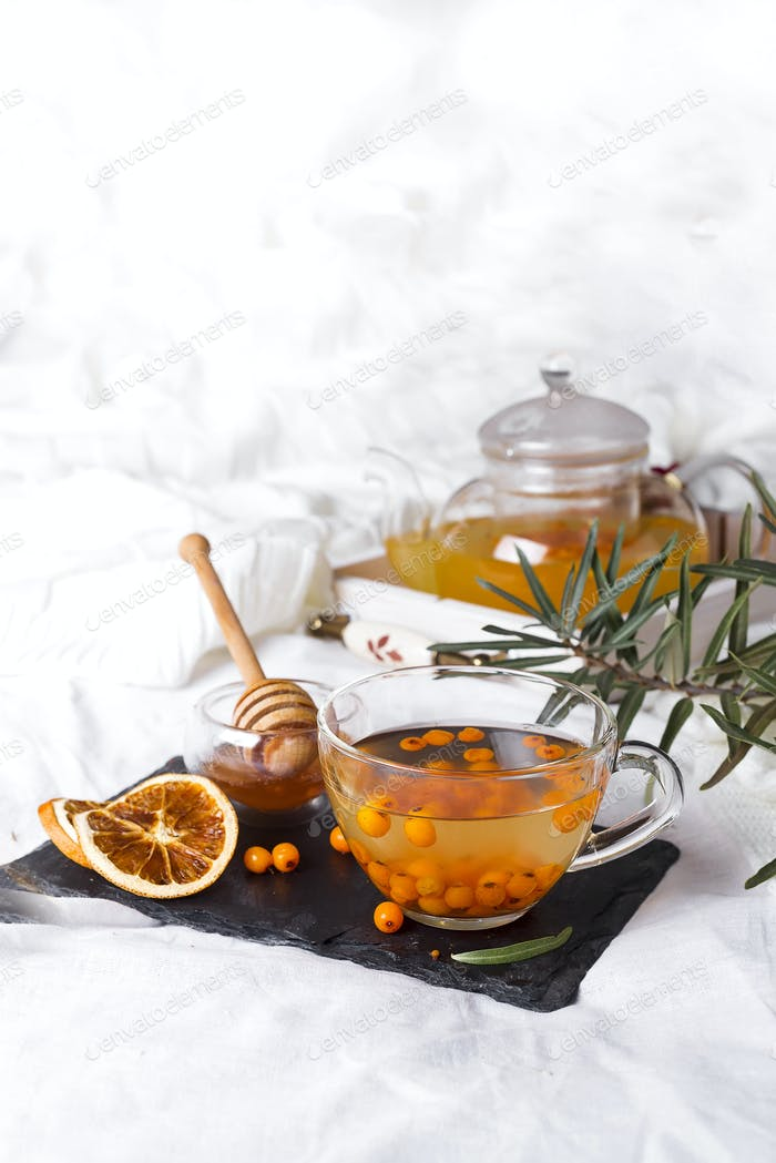 A glass teapot with sea buckthorn