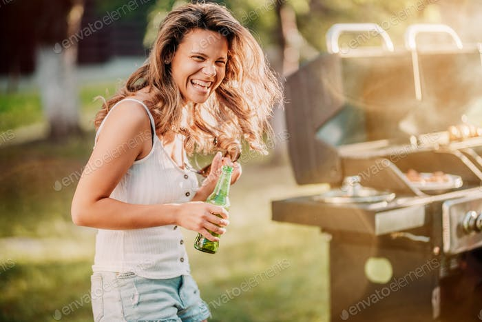 Portrait of laughing blonde girl having a great time at barbecue grill party