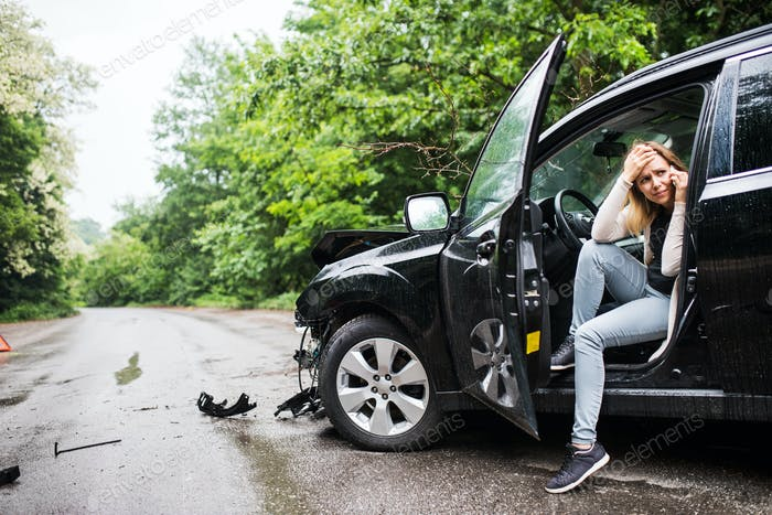 Young woman in the damaged car after a car accident, making a phone call.