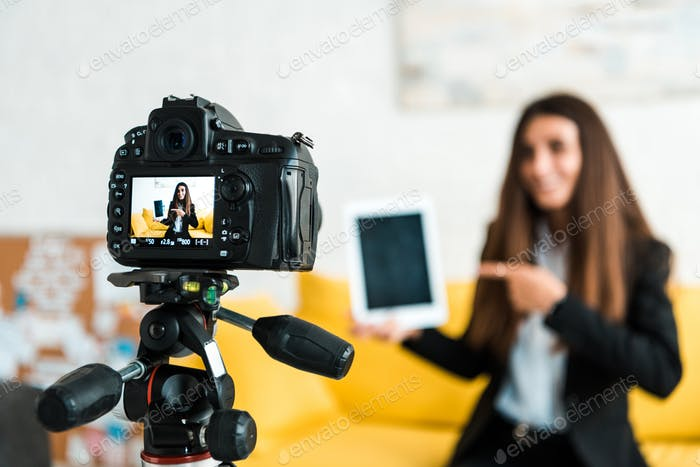 selective focus of digital camera with happy video blogger pointing with finger at digital tablet