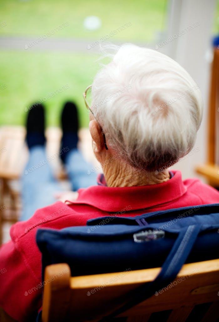 Rückansicht des Seniorenmanns sitzt auf dem Stuhl zu Hause