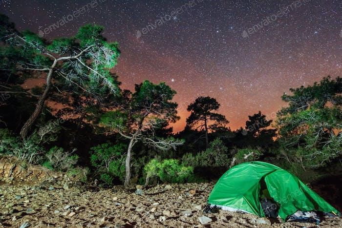 Camping under the stars. Green solo tent dark night sky