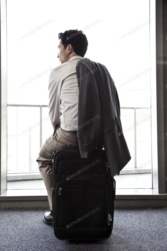 Businessman sitting on his luggage waiting for an airplane.