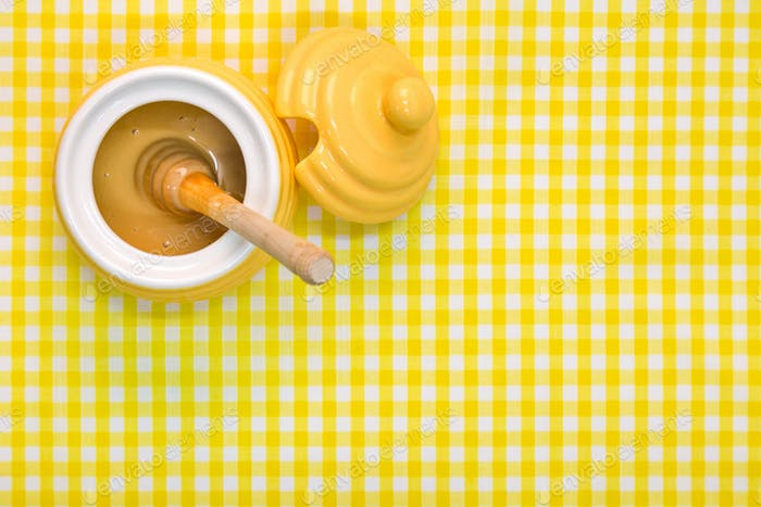 Honey pot and dipper on yellow background with copy space.