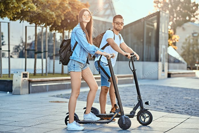 Young couple is enjoying electro scooter's riding