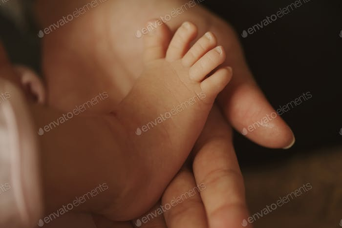 mother holds little foot of newborn baby